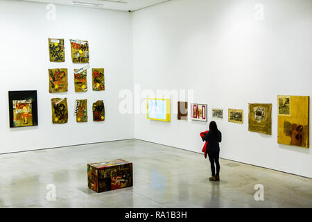 A woman seen walking front of pieces of art works of Boris Lurie Pop-art after the Holocaust exhibition. Boris Lurie (1924-2008) is an American artist of Jewish origin who was born in Leningrad (today St. Petersburg). In August 1941, the Germans began deporting the local Jewish population to the ghetto in Riga, where Boris Lurie spent his childhood. His Grandmother, mother, sister and beloved  were shot in a forest near Rumbuli in the Riga suburbs in December 1941. his work is closely related to this experience during the Holocaust. The motifs appearing in his works are photos from concentrati - Stock Photo
