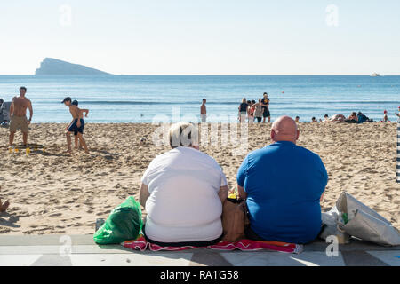 Benidorm, Spain. 30 December 2018. British tourists mix with locals on the beaches and in the bars and restaurants as they escape the cold British weather and head south to Spain. High temperatures meant that the beaches were busy from early morning with families enjoying the calm sea and temps of about 17 Celsius. Obese man and woman sitting facing the sea in this popular Spanish resort. Credit: Mick Flynn/Alamy Live News - Stock Photo