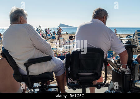 Benidorm, Spain. 30 December 2018. British tourists mix with locals on the beaches and in the bars and restaurants as they escape the cold British weather and head south to Spain. High temperatures meant that the beaches were busy from early morning with families enjoying the calm sea and temps of about 17 Celsius. middle aged couple sitting an a disability scooter on the promenade in this popular Spanish resort. Credit: Mick Flynn/Alamy Live News - Stock Photo