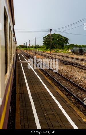 View of the railroad tracks in Thailand from a train car. - Stock Photo