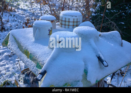 Frozen Old rusty cast metal Casseroles on a table under the snow during the winter. Photographed close-up in winter - Stock Photo