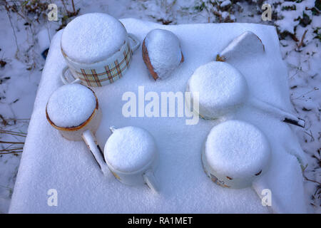 Frozen Old rusty cast metal Casseroles on a table under the snow during the winter. Like a post nuclear cataclysm. Photographed close-up in winter - Stock Photo