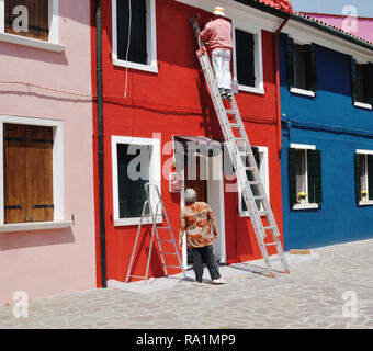A resident of Burano, an island in the Venetian lagoon, Italy, paints his house while his wife looks on. - Stock Photo