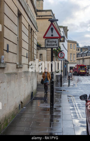 Pedestrian walking towards a triangular caution sign warning of a rising bollard in the road on Lower Borough Walls in the city of Bath - Stock Photo