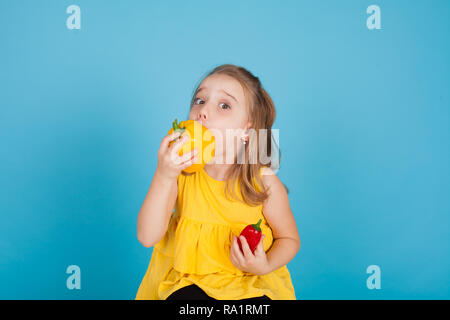 girl holding a fresh red bell pepper healthy food - Stock Photo