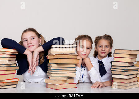 two girls schoolgirls sit with books at his desk on the lesson at school - Stock Photo