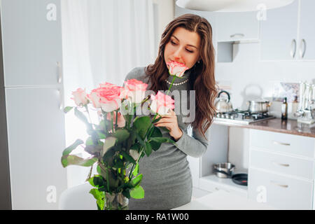 Woman puts pink roses in vase smelling flower. Young housewife taking care of coziness in kitchen. Modern kitchen design. White and silver kitchen - Stock Photo