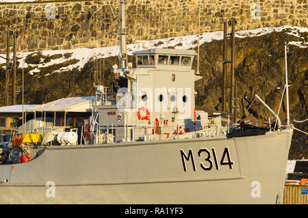 Old retired Second World War minesweeper Alta moored in Oslo harbour as museum-ship. With Akershus fortress in the background. - Stock Photo