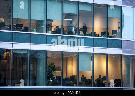 MONTREAL, CANADA - NOVEMBER 6, 2018: People working in open spaces offices in a skyscraper, seen from the outside, in the evening, in Montreal, Quebec - Stock Photo