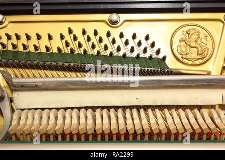 The mechanic of an upright piano, with hitch pins, strings over the bridge, a felt cloth for the mute soft (sordino) and the hammers over their shank - Stock Photo
