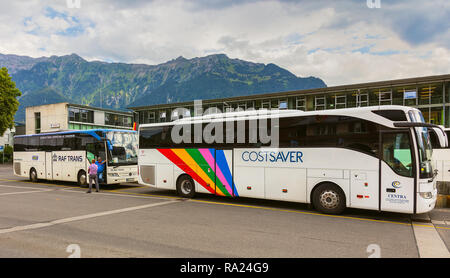Buses standing on the square at the Interlaken Ost railway station in Switzerland - Stock Photo