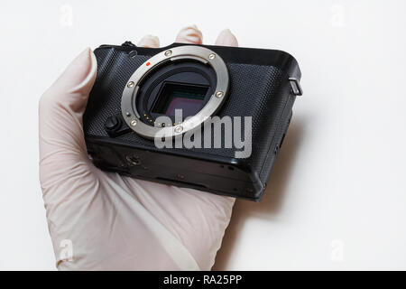 Close-up of mirrorless digital APS-C dirty camera matrix sensor cleaning and maintenance with swab, photographer cleaning photocamera on white backgro - Stock Photo