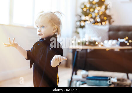 Cute toddler surprised girl in living room. Christmas tree is on background. - Stock Photo