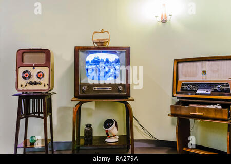 Reel to Reel player, black and white television and an old medium/long wave radio in a living room from the 1950s. - Stock Photo