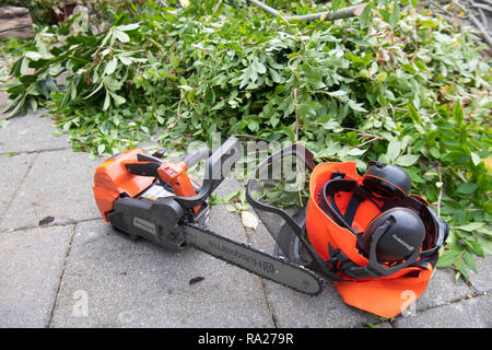 Husqvarna chainsaw and helmet with ear defenders lying on a patio beside branches which have just been cut down. - Stock Photo