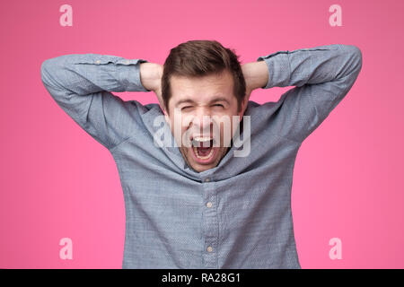 Young man covering his ears and shouting. - Stock Photo