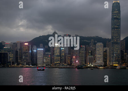 The bright red sails of the Duk Ling tourist junk accents the lights of the skyscrapers that fringe Hong Kong harbour. - Stock Photo