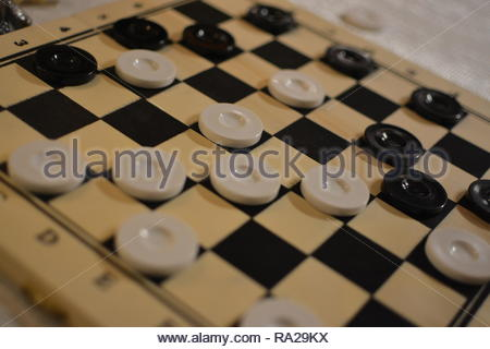 Closeup of drafts (checkers) pieces on a wooden gaming board. Drafts is similar to chess however with fewer rules is easier to pick up and play. - Stock Photo