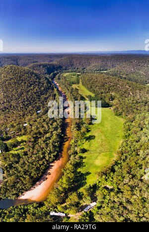 Overhead top down view over river stream of Colo River around Colo Heights area of the Gread Dividing range in Australia in vertical panorama under bl - Stock Photo