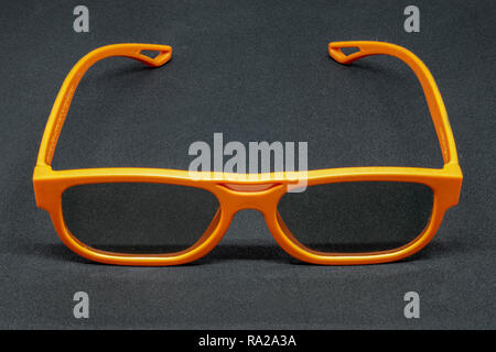 Orange 3 Dimensional glasses on a dark grey background - Stock Photo