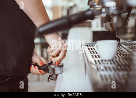 Barista presses ground coffee using tamper. Close-up view on hands - Stock Photo