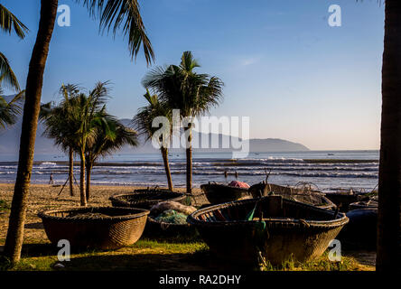 Early morning sun on the round fishing boats that the Vietnames use. These are parked in the sand - Stock Photo