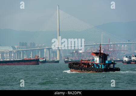 A colourful tugboat navigates the busy shipping lanes around Stonecutters Bridge and Tsing Yi's container terminal in Hong Kong. - Stock Photo