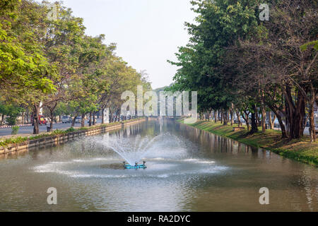 A part of the moats which surround the centre of Chiang Mai old city and its outer walls (Thailand). Here, the intense car traffic is particular: - Stock Photo