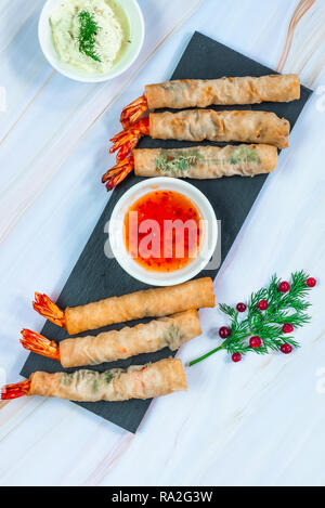 Giant king prawns with sweet chili and yogurt dipping sauces. Party food idea. Top view. - Stock Photo