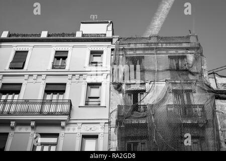 An old derelict building covered in green netting next to a restored and renovated building in the Old Town of Valencia, Spain. - Stock Photo