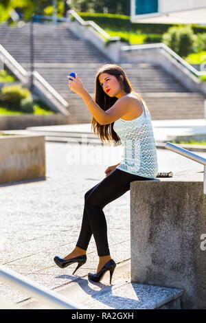 Standing outside looking at handy small mirror fixing hand-brushing long brunette hair attractive young woman 20s twenties Black tight pants - Stock Photo