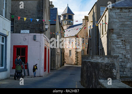 The narrow streets of downtown Lerwick, Shetland Islands,  with stone architecture and cheerful bunting - Stock Photo