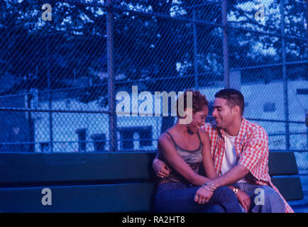 Young Urban ethnic couple flirting on a park bench at dusk or early evening - Stock Photo