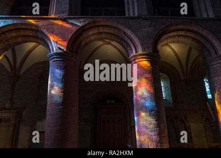 Interior arches of St. Magnus Cathedral in Kirkwall are lit up by a rainbow of light coming through the stained glass windows of the western facade - Stock Photo