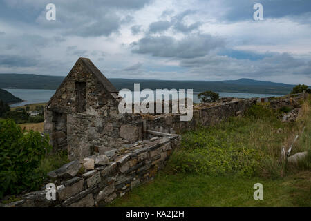 An abandoned ruin of a croft house overlooking the Kyle of Tongue in the Scottish Highlands of Scotland on a cloudy day - Stock Photo