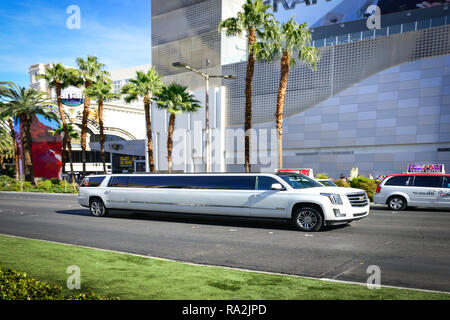 A white Cadillac stretch limousine traveling on the Las Vegas Strip in front of the Linq Hotel and Casino in Las Vegas, NV on a sunny day - Stock Photo