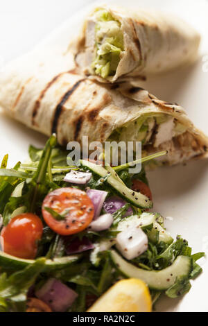 Grilled chicken wrap served with greek salad on a bright and white plate. - Stock Photo