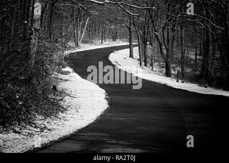 A country road curves uphill surrounded by snow in winter, black and white - Stock Photo