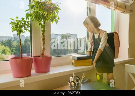 Little girl student with backpack in school uniform looks out the window, background is children's room, desk, computer. School, education, knowledge  - Stock Photo