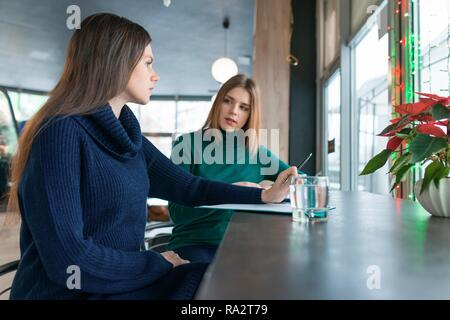 Woman psychologist counseling talking to a young girl, psychotherapist gives psychological help in cafe coffee shop. - Stock Photo