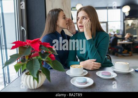Two young beautiful women secretly sitting at a table in a coffee shop, girls whisper a secret in their ear. - Stock Photo