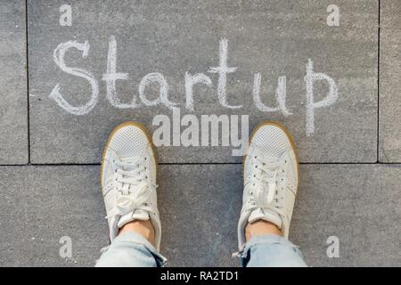 View from above, female feet with text startup written on grey sidewalk. - Stock Photo