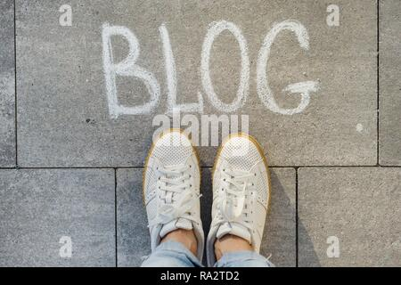 View from above, female feet with text blog written on grey sidewalk.