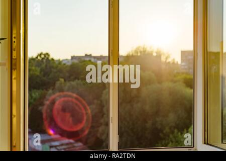 Open windows in the apartment. Background evening sunset, city silhouette. - Stock Photo