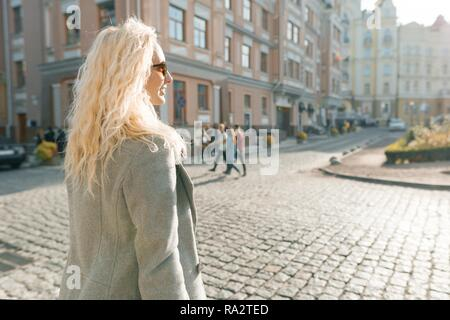 Closeup outdoor portrait of young smiling blond woman with sunglasses with long curly hair. On city street sunny day. - Stock Photo
