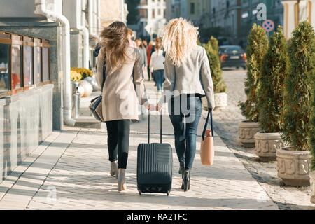 Two young women with a suitcase walking along city street, sunny autumn day, golden hour, view from the back. - Stock Photo