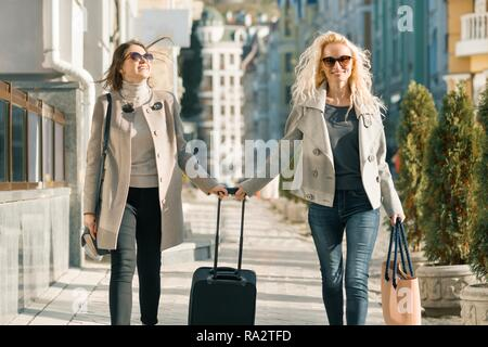 Two young smiling women with a suitcase walking along city street, sunny autumn day, golden hour. - Stock Photo