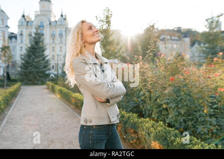 Closeup outdoor portrait of young smiling blond woman with long curly hair. On city street sunny day.