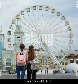 Two young girls with backpacks looking at the Ferris wheel, back view, in the city. - Stock Photo