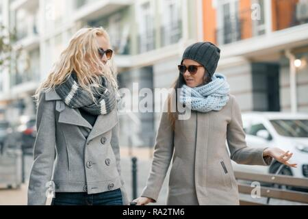 Two young smiling beautiful women in warm clothes walking down the city street with a travel suitcase, women laughing and talking. - Stock Photo